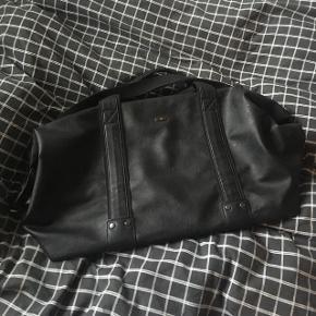 Sort rejsetaske. Tasken er aldrig brugt, og fejler derfor intet. Mål: længde: 53 cm, højde: 30 cm, bredde (når der er ting i tasken): 25 cm. Indvendig er der en lille lynlåslomme, og tasken har en skulderrem. Nypris var 800 kr.  Køber betaler fragt