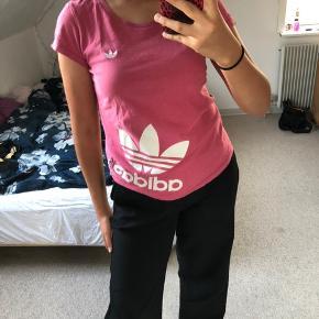 Ret fed Adidas T-shirt i en stærkt lyserød farve, med mærket trykt ned ad siden og broderet på brystet. Den har et feminint Cut og er derfor ret tætsiddende og har korte ærmer. Fitter xs/s og en lille m