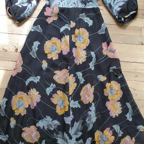 Vintage retro selskabs kjole fra 70'erne af mærket Mag Fortail Paris. Den måler 74 på det smalle stykke lige under brystet, 150 om rumpen og den er 142 lang. Den har bindebånd i ryggen og farverne er sort, grå, rosa og okker.