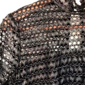 Super flot Kylie Silver bluse fra AJ Project. Blusen er i sort og sølv med høj hals og lange ærmer. Den er med struktureret mønster og er transparent på ærmerne og på blusens øverste stykke. Blusen går et stykke længere ned på ryggen og er med en lille slids og en knap i nakken.  Blusen er brugt en enkelt aften og fremstår som ny.