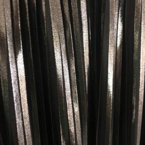 Passer også en str. L😊 elastik i taljen. Plisseret i sort og sølv. Holder formen ved vask.