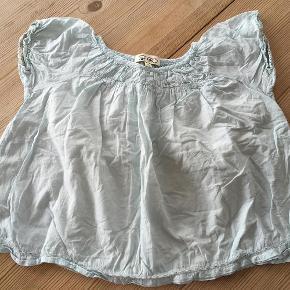 Varetype: bluseStørrelse: 8år Farve: Lyseblå Oprindelig købspris: 350 kr.  Sød overdel fra Gro. Den er vasket én gang, men aldrig brugt, og fejler dermed intet!  OBS: Blusen er mintblå. Billedet af den gule top er bare for at vise, hvordan den ser ud på. :)