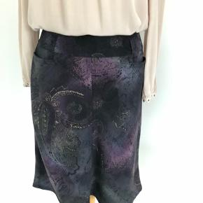 Flot nederdel fra Che Donna med abstrakt mønster i lilla, blå, sort, grå og grønlige nuancer med en diskret sølvtråd. To forlommer og et fast, bredt stykke foroven, hvor der også er bæltestropper. Lukkes med lynlås bagtil. Længde er 58 cm, og livvidden er 68 cm. Fremstillet af polyester. Bærer ikke præg af brug.