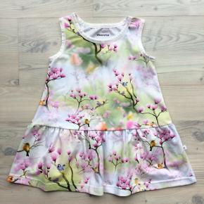 Fra egen systue:  Ærmeløs kjole i blødt bomuldsjersey. Digitalprint af fugle, blomster og grene. Hvid foldeelastik i hals og ærmegab. Bomuldsjersey - 92 % bomuld og 8 % elasthan. Øko-Tex 100 certificeret. Det anbefales at vaske tøjet ved 30 grader og undgå tørretumbling.  Str. 98.  Vibserarius (eget design)