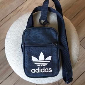 Jeg sælger denne Adidas taske, da den bare hænger. Den er ikke brugt særlig meget, og den fejler ingen ting.   Kom gerne med bud!