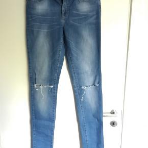 Kun brugt gange få gange og fremstor derfor i god stand. Jeansne er mid waist og rippet ved knæene.
