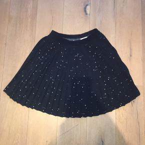 Smuk, mørkeblå nederdel med plissering og Hvidt mønster. Aldrig brugt.