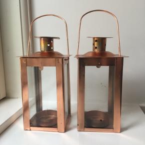 To små bronzefarvede lanterner til stearinlys. Lanterner har glas hele vejen rust og en lille hank. Toppen kan vippes af, så man kan sætte fyrfadslys i. Kan bruges både udendørs på terrassen, på altanen eller som rustikke fyrfadslysestager indendørs.   Har noget patina på begge stager.   Mål: H: 11,5 cm, B: 6,5 cm  Pr. stk 20 kr. Sælges samlet for 30 kr.