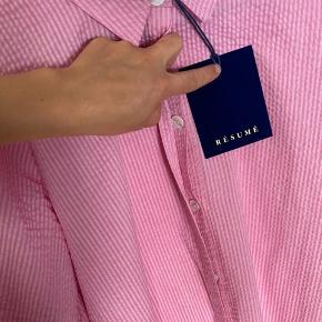 Smuk Urban kjole i bæk & bølge fra Resume. Kjolen er a-formet med korte ærmer med puff og v-udskæring.Kjolener i pink med lyserøde striber, den har krave i halsenogskjult knapper fra halsen og ned foran.Kjolen har 3/4 ærmer med elastik forenden. Der er slids op foran og i begge sider. Kjolen er længere bagtil end fortil.  Materiale: 65% Polyester, 35%Cotton  Mål: Bryst omkreds: 48 cm Længde: ca 120 cm  Respekter venligst at jeg ikke bytter og køber betaler porto samt gebyr ved tspay.