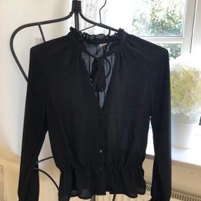 Utrolig flot skjorte/bluse med sløjfe ved kraven og indsnævring ved taljen   Den fejler ingenting