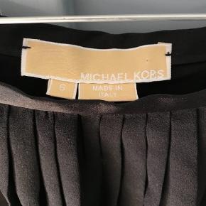 Rigtig fin, sort Michael Kors nederdel med plissé i tre lag samt underskørt. Lynlås og hægte i siden. Str.36 (s/m). Kun brugt få gange, og fremstår som ny.  Midi Farve: Sort