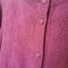 Vintage cardigan med søde lommer. Farven, cherise, fremgår på sidste billede. 15% uld, 73% akryl, 12% polyamid. Af mærket Quimo Passer fint str. M-L