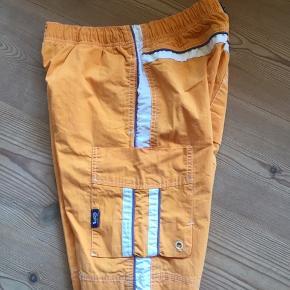 Badeshorts/ shorts i en lidt brændt agtig orange farve, med smarte detaljer og god pasform. 6705 Esbjerg