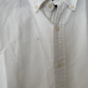 Skjorten fremstår stort set ubrugt, dog har den en lille sort plet, som også ses på billedet. Denne kan evt fjernes ved rens.