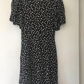 Sød sort kjole med hvide prikker, knaplukning ved høj hals og sådan lidt løse flagermuse ærmer.
