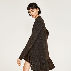 """Smuk """"tung"""" vævet kjole fra ZARA i sort med kobbertråd og skød/Svaj forneden. Den er en str.38/medium - den er aldrig brugt. Den kostede 450 for ny.  Respekter venligst at jeg ikke bytter og køber betaler porto samt gebyr ved tspay."""