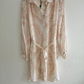 Smuk silkekjole / skjortekjole fra Intropia.Geometrisk printdesign med krave og lange ærmer.Lette silhuet, lommer og bånd i taljen.