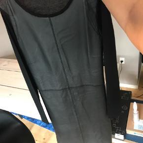 Varetype: Andet Farve: Sort Oprindelig købspris: 1600 kr.  Super fed KBS kjole, aldrig brugt. Foran er 100% læder og bagsiden og ærmerne er 100% uld. Den er en smule længere foran end bagpå.  Bytter ikke.