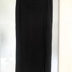 Knælang nederdel med slids i siden.