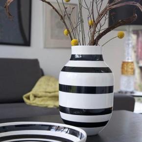 Den klassiske og karakterfulde Kähler Omaggio Vase, der er stor nok til at indeholde høje og sofistikerede blomster i en blandet buket. De håndmalede sorte striber, der nydeligt pynter den ikoniske Omaggio-vase er en stilsikker og særdeles moderne tilføjelse til det skandinaviske hjem. Vasen kan pynte på spisebordet, reolen, gulvet eller i stuevinduet med eller uden blomster.  Mål: H31 cm Stand: helt ny og ubrugt  Nypris: 400 DKK