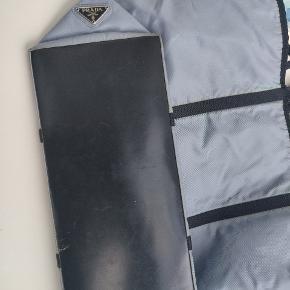 Lyseblå Prada Skuldertaske. Der er en indbygget velcro holder i den som ses på 1. Billede, til diverse ting. Den har lidt misfarvning blandt sygningerne, men det er meget svagt.