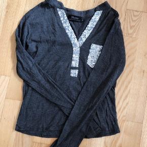 Fineste grå bluse med sølv detaljer fra mærket Motto Copenhagen Lille i størrelsen så passer bedre en størrelse  xs/s  Afhentes 8000 Aarhus C  Eller sendes med Dao for 38kr.