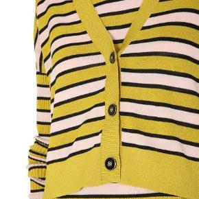 Feminin kort cardigan med striber i gul, nude og sort. Cardiganen har V-udskæring med ribkant og lukkes foran med 3 flotte knapper, drop shoulder og lange ærmer i rib.    MATERIALE: 50% Tencel 21% Metal Polyester Film 29% Polyester