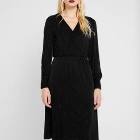 Meget velsiddende kjole, der falder så flot og har en smuk halsudskæring (lukkes med en lille haspe) Fin med sølv lurex striper - perfekt til nytårsaften. Kun brugt 1 gang.