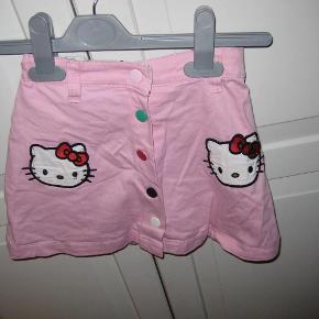 Supersød nederdel med trykknapper.. Regulerbar elastik i taljen.  Se også mine andre annoncer.  Nederdel med Hello Kitty Farve: Lyserød