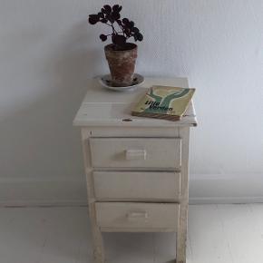 Fint lille sengebord fra ca 1940'erne - 1950'erne sælges.  Lille sengebord i form af kommode med tre skuffer. Måler 33 x 33 x 54 cm. Hvidmalet træ.   Afhentes hos mig på indre Nørrebro i København.
