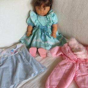 Fin dukke med langt mørkt hår, er 50 cm lang. Der medfølger kjole og skidragt.