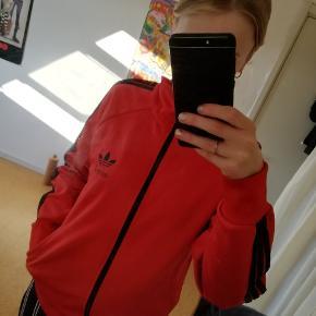 Adidas trøje i rød med sorte striber Brugt få gange og standen er helt som ny Str M men jeg er normalt en str S Bud ønskes
