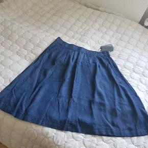 Skøn blød denim nederdel,str 44 fra Fransa.  Aldrig brugt. Mærke er på endnu  Der er lommer og en lynlås i siden.   Længde 68cm. Pris 150kr.  Hentes i Nørresundby eller sendes med DAO for 37kr