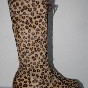 Varetype: Flotte støvler - den lange model Farve: Leopard  Flotte lange støvler i leopardfarvet pels. Og med de stødabsorberende såler, som Bumper er kendt og elsket for. Ikke mindst fordi de også er gode til at holde varmen i den kolde tid.  Støvlerne er brugt 3-5 gange, så de fremstår stadig næsten som nye DOG - vil jeg gerne henlede din opmærksomhed på at de originale snørebånd og lukkemekanismen til snørerne ikke længere er. I stedet har min datter erstattet dem med lidt tyngere snører. Udover dette har jeg intet at udsætte på disse flotte støvler.  Sålen der kan tages ud måler 23,2 cm.  Jeg har ikke længere har den originale skokasse. Men at de selvfølgelig vil blive sendt på fuld forsvarlig vis.  Prisen er fast, og de sælges til den første som trykker på køb-nu-knappen eller byder prisen.  Den opgivne pris på forsendelse fordrer forsendelse med DAO. Ønsker du dem sendt med Postnord gør jeg det hjertens gerne. Men så er prisen en anden.  Jeg mailer meget gerne flere billeder af støvlerne, også indersiden, som er lige så flot som ydersiden. Du siger bare til....  Bemærk venligst, at jeg ikke bytter med andre varer, beklager.
