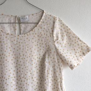 Hvid bluse med lyserøde og guld prikker. Nogle få af guld prikkerne har en mørk prik (sidste billede)