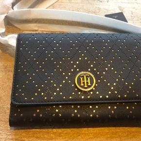 """HELT NY crossbody taske fra TH, i original indpakning og med mange funktionsmuligheder, bla remmen kan tages af så den kan bruges som clutch. Der er møntrum og plads til kort, yderligere er der """"taskerum"""".   Farven er mørkeblå/guld."""