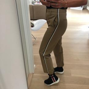 Bukser med pressefolder og track striber. Store i størrelsen og passer også 38.