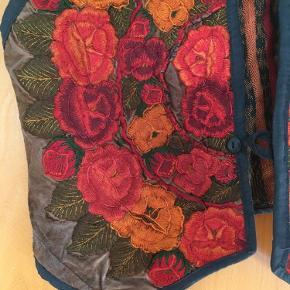 Meget smuk vintage - retro vest med fantastiske blomster broderier. Passer en s og m. Længe 58 cm, bredde 2*47 cm.