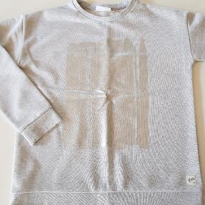 Gråmeleret sweatshirt med sølvglimmer og sølvprint foran. Længde ca 55 cm. Bredde ca 45 cm.  Sender også. Det koster 38 kr.