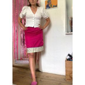 Sødeste Ganni nederdel i pink og champagne farvet shiny tekstil. Med sødt bånd i lyseblå med små blomster i pink og lyserød med grønne blade. Lukkes ved hæfter i den ene side. Så fin til sommeren eller med et par sjove strømpebukser under.  Sælges da jeg ikke får den brugt. Passes af XS - S.