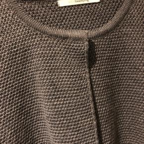 Lækker klassisk strik cardigan i kort let a-facon med lommer i siderne. Mellem grå, 59% merinould, 50% acryl. Ingen brugsspor.....