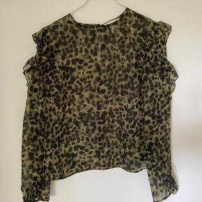 Flot og populær skjorte / bluse med flæser fra H&M. Lidt transparent. Fejler absolut ingenting. Husker ikke nypris.
