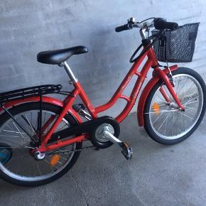 """Fin rød pigecykel med 3 gear, fodbremse, håndbremse til forhjul, cykelkurv og ringklokke. 20"""" hjul. Brugt, men i god stand."""