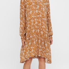 Skøn kjole fra Second Female i en smuk ørkenbrun farve og med print af blomster. Mindy Dress har flæsekant i hals og ærmekanter og en løs pasform med fine flæsedetaljer. Der medfølger aftagelig ørkenbrun underkjole.  Mindy kjolen er super fin med en stilet til sæsonens finere begivenheder, men også skøn på sommerdage med bare ben og en sandal.  100% Viscose underkjole: 100% viskose skånevaskes ved 30 grader
