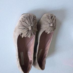 Skønne sandfarvet ruskinds ballerina med blomst. Har elastik rundt om hælen for komfortabel pasform. Foret med rosa skind. Beige/grålig Pæn stand. Ikke brugt meget.