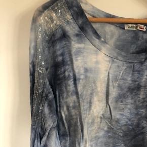 Tag 3 og betal for 2. Gælder de annoncer, hvor det er anført.   Sælger denne bluse i blå nuancer. Rund hals, loose fit og palietter på skuldrene.   95% bomuld og 5% elastan.   Køber betaler evt porto, der tillægges prisen. Jeg sender med Dao.   Str. One size  Bluse Farve: Blå