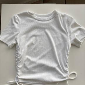 Super sød t-shirt fra Zara med snøre i siderne der kan justere længden på trøjen. Aldrig brugt derfor ingen brugstegn eller skader. Str. Medium, hvid