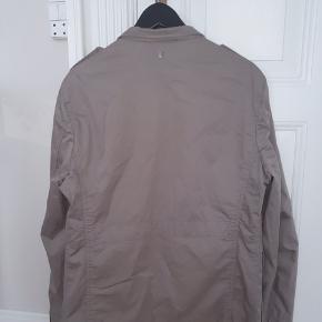 En enkel knap er faldet af og mærket indeni hænger på en tråd. Ellers er jakken generelt i rigtig fin stand.
