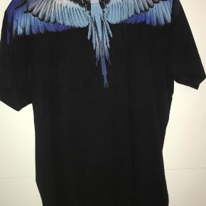 Velholdt og flot Marcelo Burlon tshirt i sort med farver på ved halsen. Brugt én gang.  Str. XS, men meget stor i størrelsen og derfor brugt af en str. M.  Nypris var 1800kr, sælger for min. 750 Byd