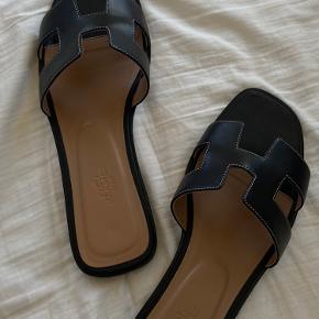 Smukke Hermes Oran sandaler i sort.  Størrelse 40, men fitter også 38/39 De er brugt 2 gange og der er ingen tegn på slid. Nypris er 4000 kr.  Pris 3000 kr.  Flere billeder kan fremsendes.